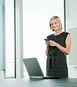 A smiling woman holding a phone with a laptop on a table